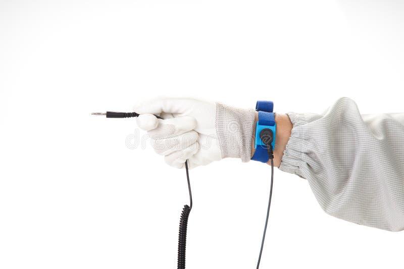 在佩带ESD布料和手套stati的一个人的手上的镯子 免版税库存图片