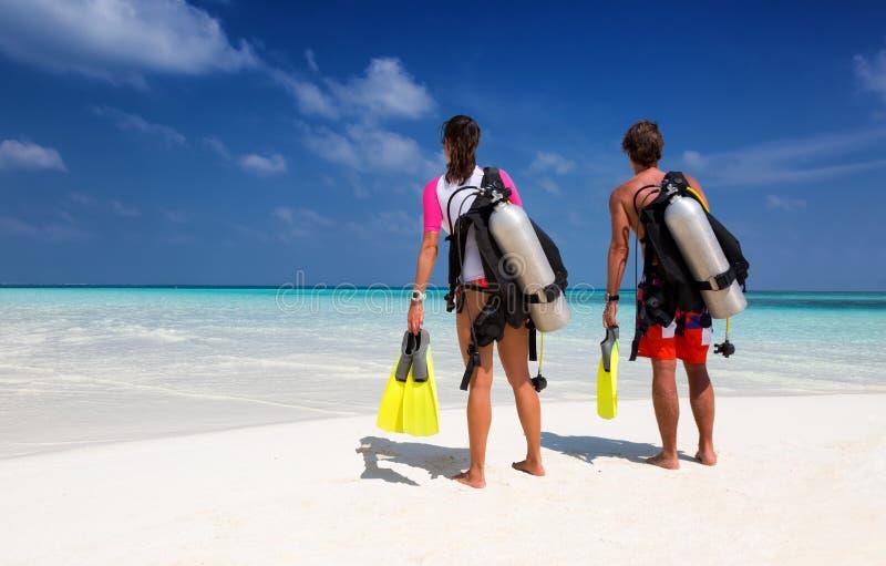 在佩戴水肺的潜水齿轮的年轻夫妇 免版税库存图片