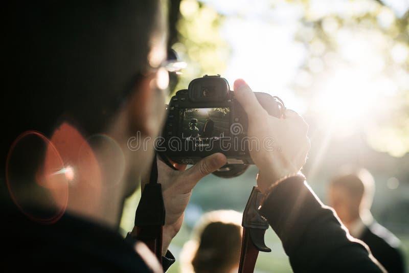 在佳能照相机的摄影师射击在夏天 免版税库存图片