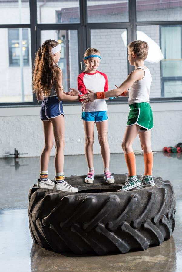 在使用在健身演播室的运动服的可爱的滑稽的孩子 免版税库存照片