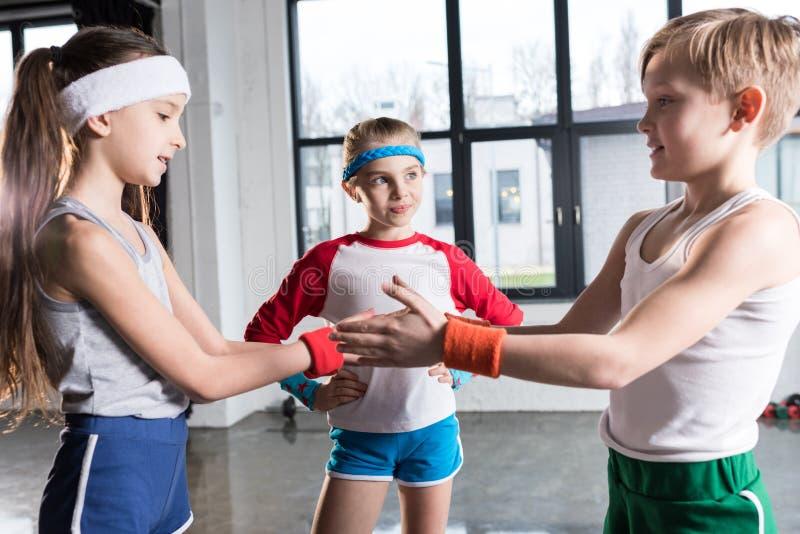 在使用在健身演播室的运动服的可爱的滑稽的孩子 免版税库存图片