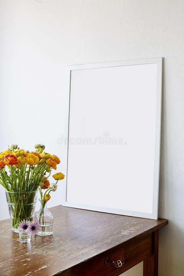 在使用的木桌上的大框架与毛茛开花 库存图片