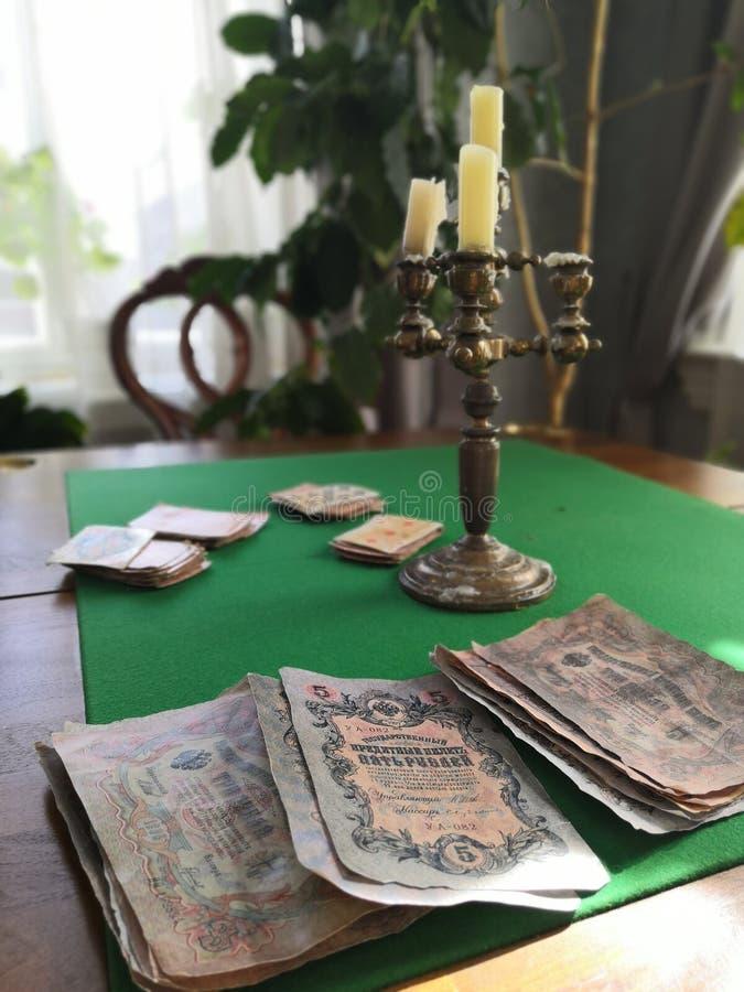在使用的桌上的老烛台与卡片和金钱 图库摄影