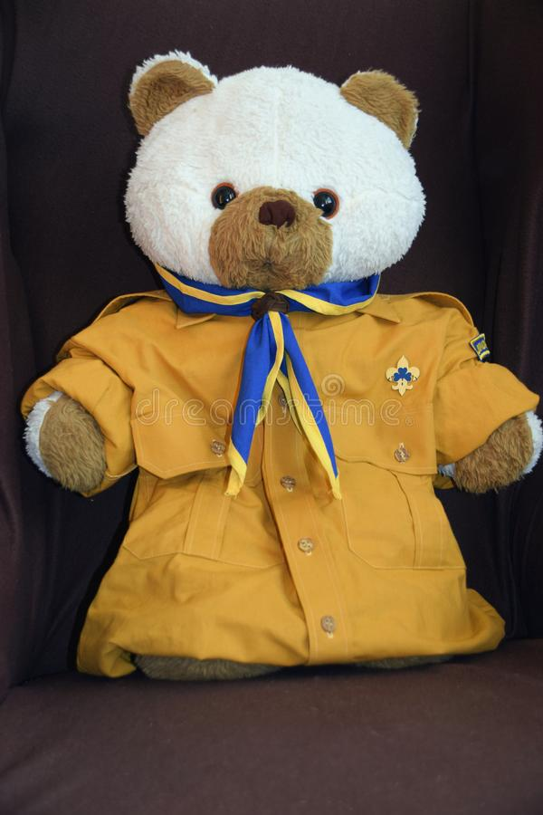 在侦察员衬衣和围巾穿戴的玩具熊在椅子 免版税库存照片