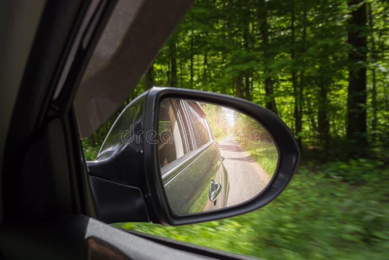 在侧视图镜子的一个看法 镜子后方汽车 路的反射 库存照片
