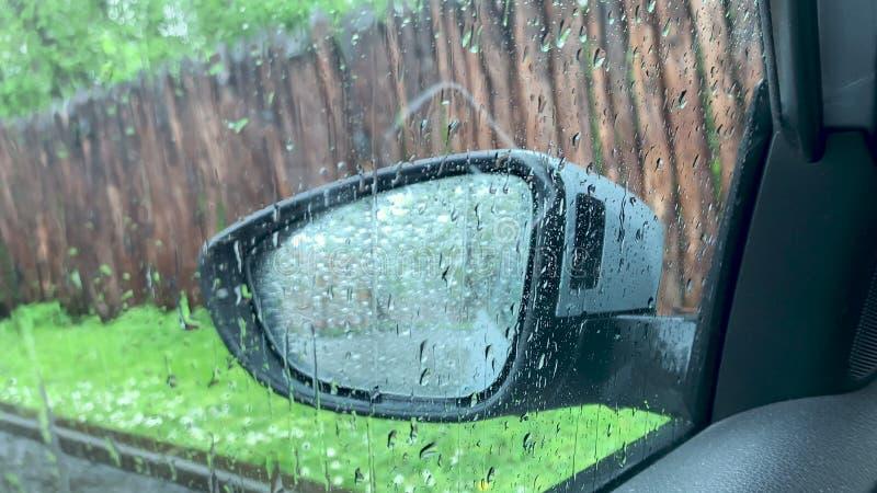 在侧面窗和汽车镜子的雨珠 库存照片