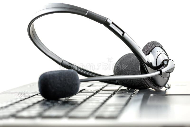 在便携式计算机上的耳机 库存照片