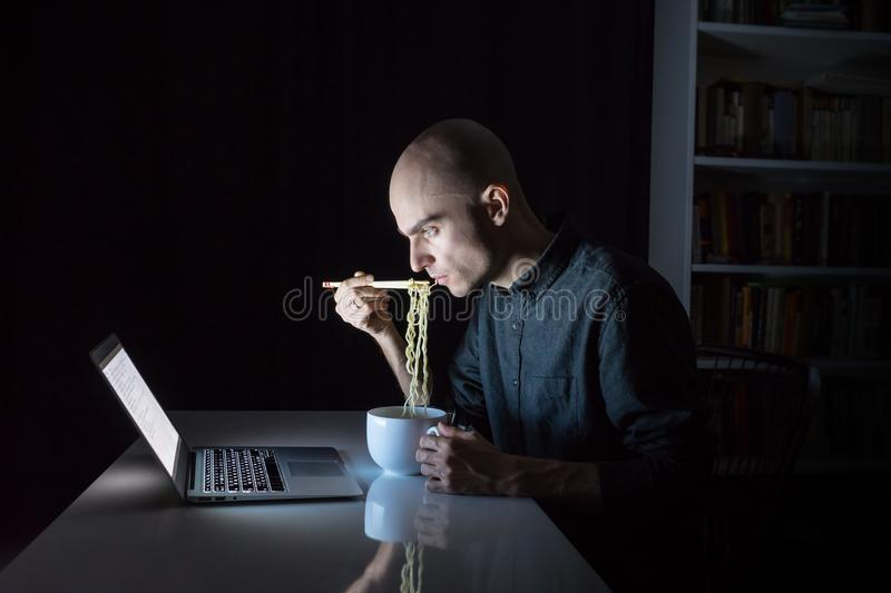 在便携式计算机的年轻男性吃立即拉面面条 免版税库存图片