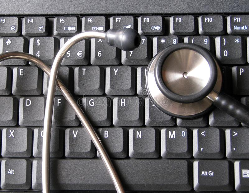 在便携式计算机键盘顶部的医疗听诊器 说明医疗保健和技术,信息学,分析复杂生物资料的学科 免版税库存照片