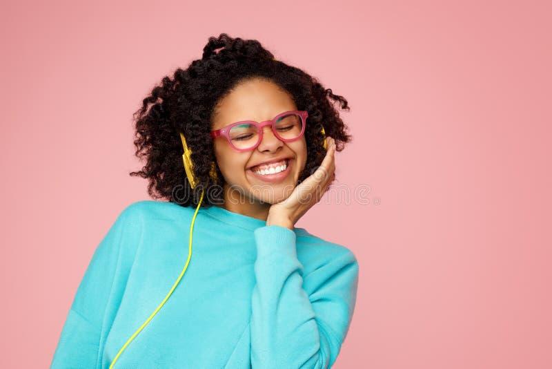在便服、玻璃和耳机有灿烂微笑的美丽的非裔美国人的年轻女人打扮的在桃红色 免版税库存图片
