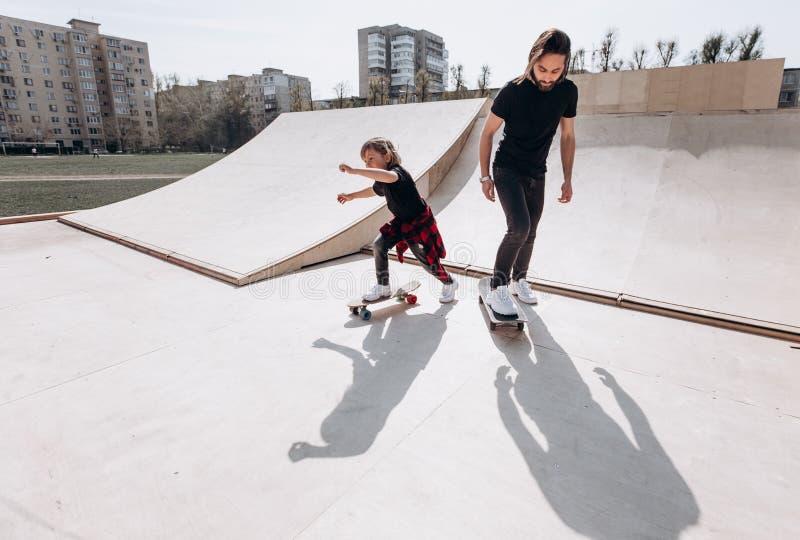 在便服和他的小儿子打扮的父亲在好日子乘坐滑板在有幻灯片的一个冰鞋公园 库存图片