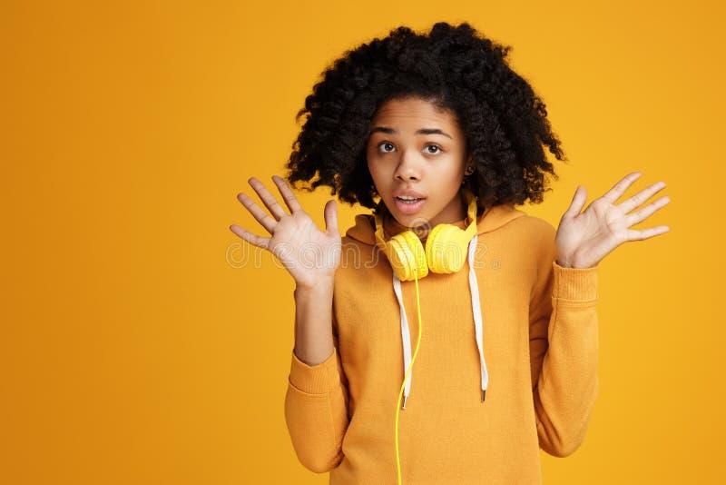 在便服和耳机打扮的震惊非裔美国人的年轻女人在黄色背景 库存图片