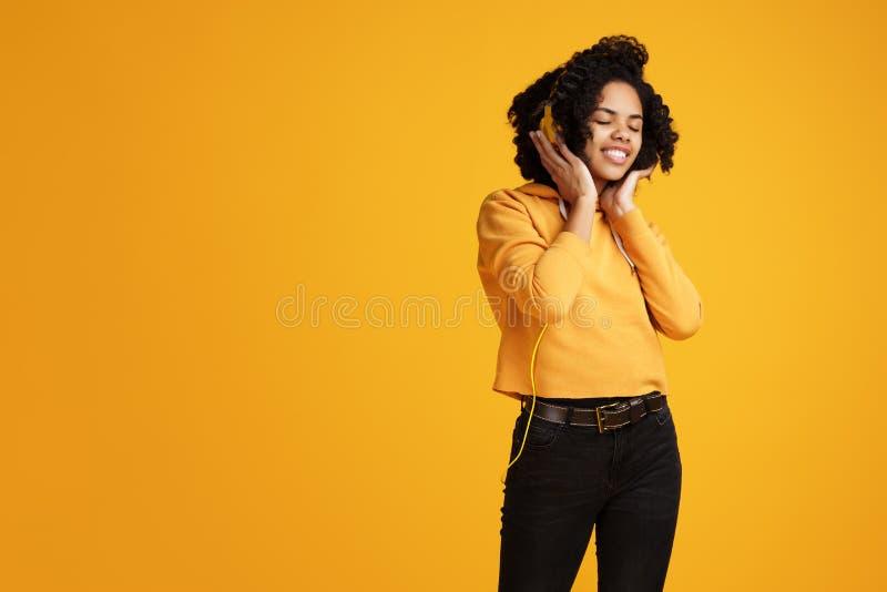 在便服和耳机衣物听的音乐有灿烂微笑的时髦非裔美国人的年轻女人打扮的 库存照片
