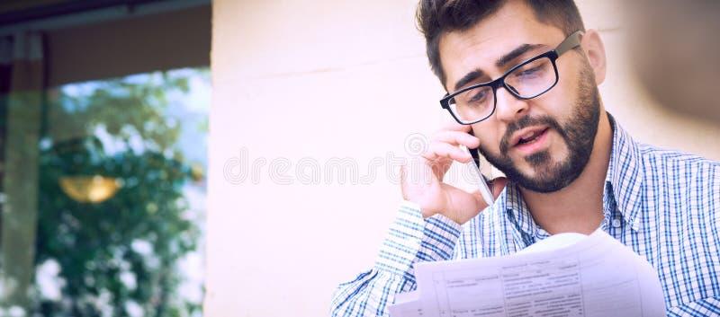 在便服和镜片的年轻有胡子的商人学习文件,当谈话在智能手机坐时 库存图片