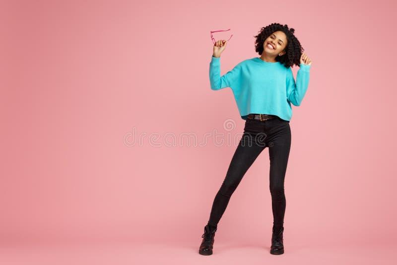 在便服有灿烂微笑的打扮的激动的非裔美国人的年轻女人充分的lengh照片,玻璃和 免版税库存照片