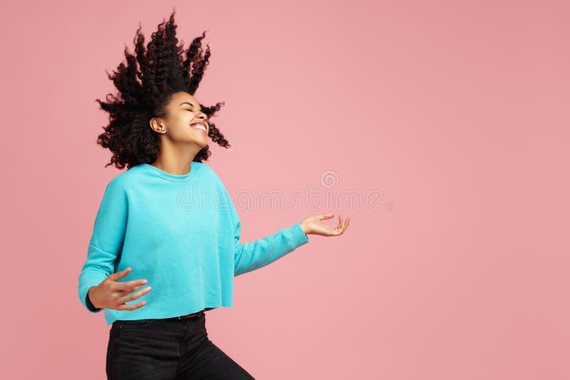 在便服有灿烂微笑的打扮的激动的非裔美国人的年轻女人画象跳舞与无形的吉他 图库摄影