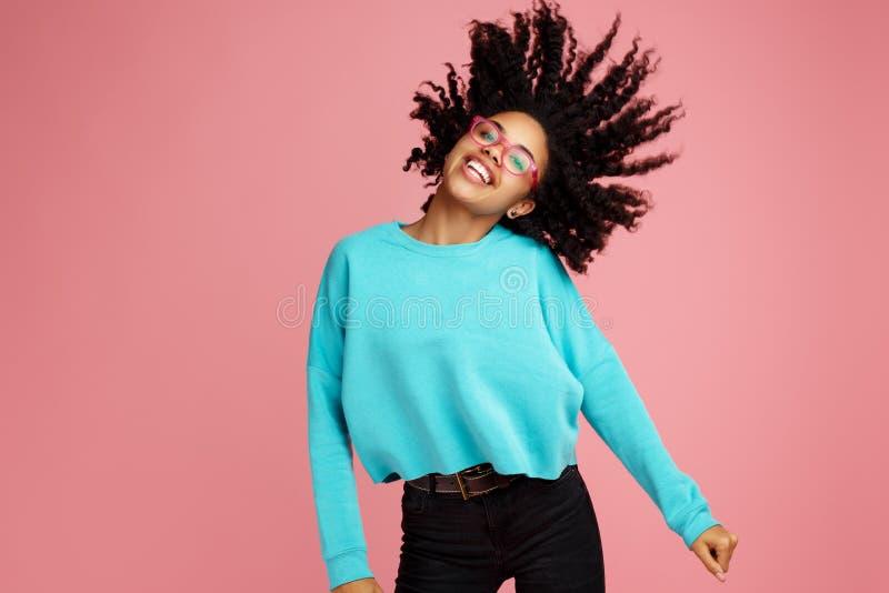 在便服有灿烂微笑的激动的非裔美国人的年轻女人打扮的,玻璃和耳机跳舞在桃红色 库存图片
