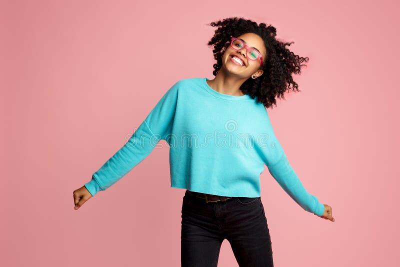 在便服有灿烂微笑的激动的非裔美国人的年轻女人打扮的,玻璃和耳机跳舞在桃红色 免版税库存图片