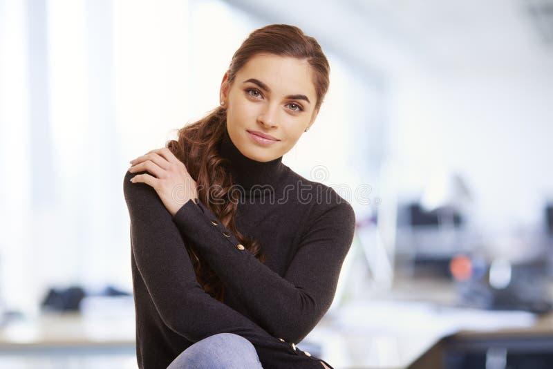 在便服的轻松的年轻女实业家画象在办公室 免版税库存照片