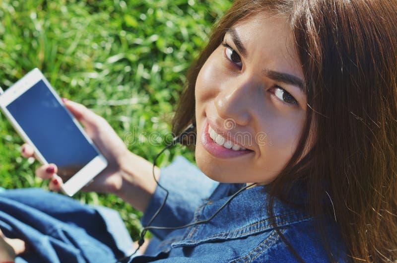在便衣打扮的年轻有天才的女生走在城市附近和听喜爱的电台 免版税库存图片
