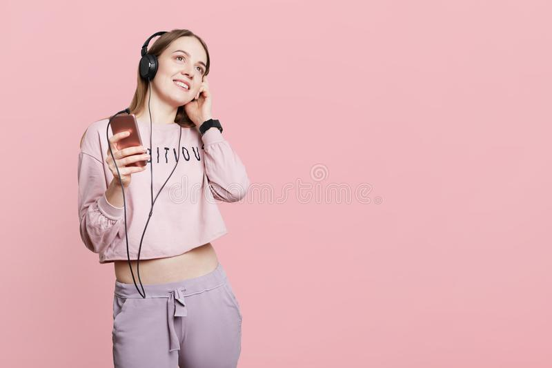 在便衣的宁静的女性模型拿着现代手机,听在耳机的喜爱的音乐,有愉快的表示, isola 免版税库存图片