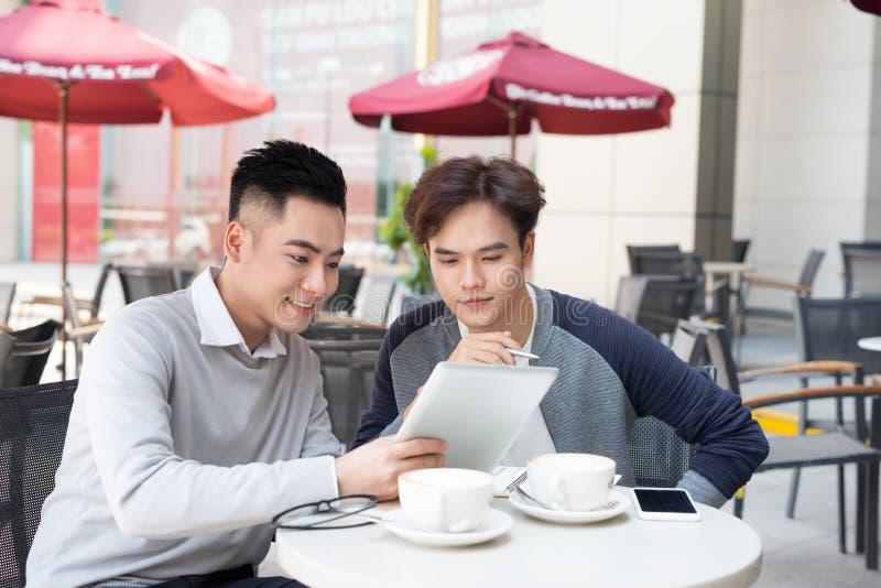在便衣的微笑两个年轻英俊的商人, talkin 免版税库存图片
