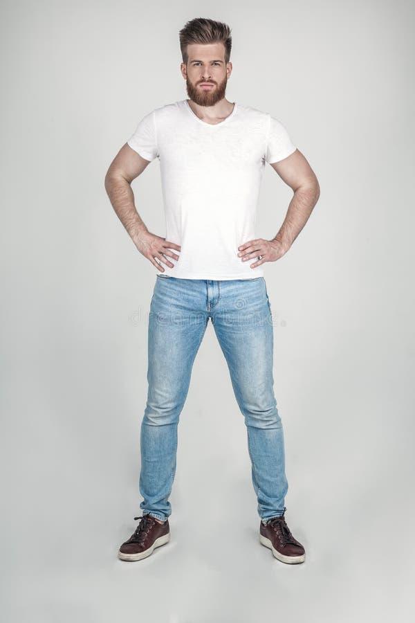 在便衣神色有胡子和一种美好的发型的一帅哥打扮的在照相机 在白色对面的立场 图库摄影