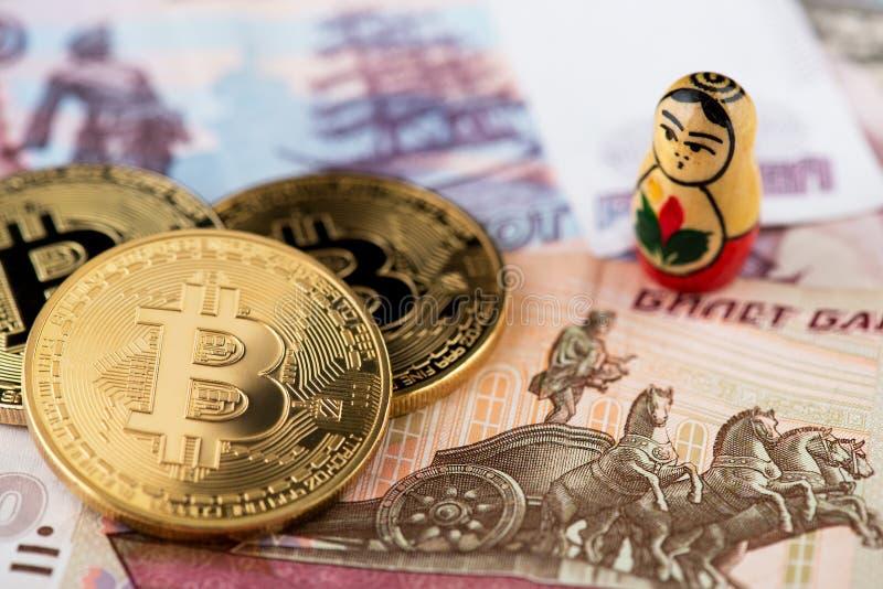 在俄国钞票的Bitcoin硬币与bitcoins的图象的俄国全国玩偶A关闭与俄罗斯卢布钞票的 库存照片