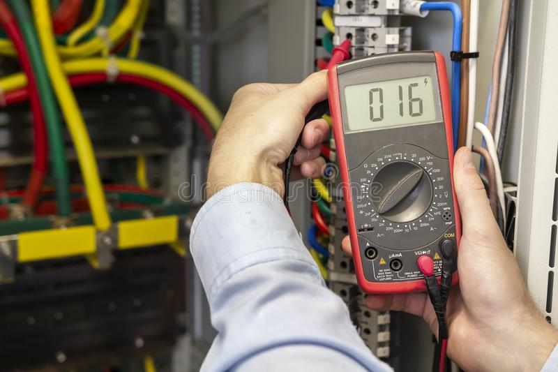 在保险丝板特写镜头的电工测量的电压 审查与多用电表探针的男性技术员Fusebox 库存图片