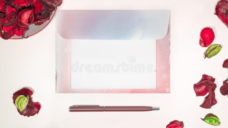 在信封的空白的公开信在有写的供应和桃红色干花一张书桌上 图库摄影
