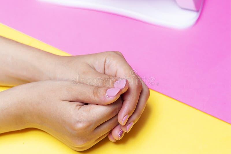 在修指甲做法以后的女性的手 指甲油艺术或紫胶的概念 库存图片