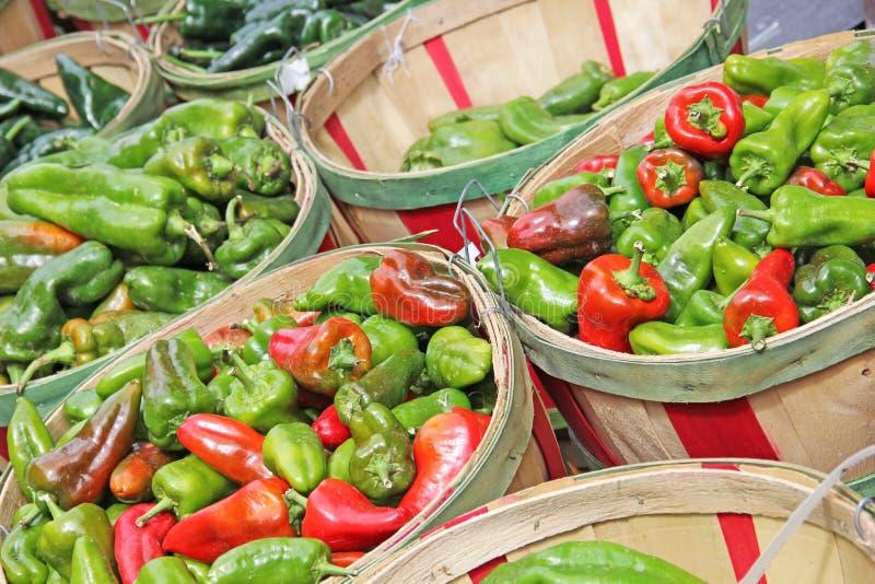 在修补篮的红色和绿色辣椒待售 免版税图库摄影