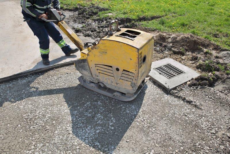 在修路站点的工作者用途振动的板材压紧机 库存图片