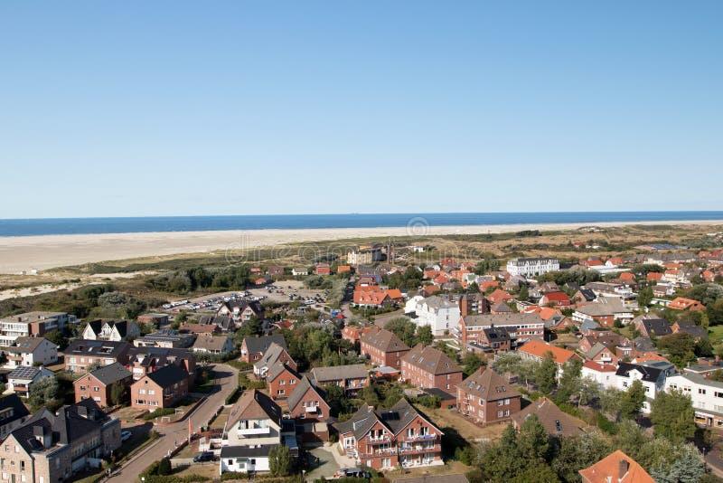 在修造的外部、海滩和北海的看法在天空蔚蓝下的天际的在北海海岛borkum 免版税图库摄影