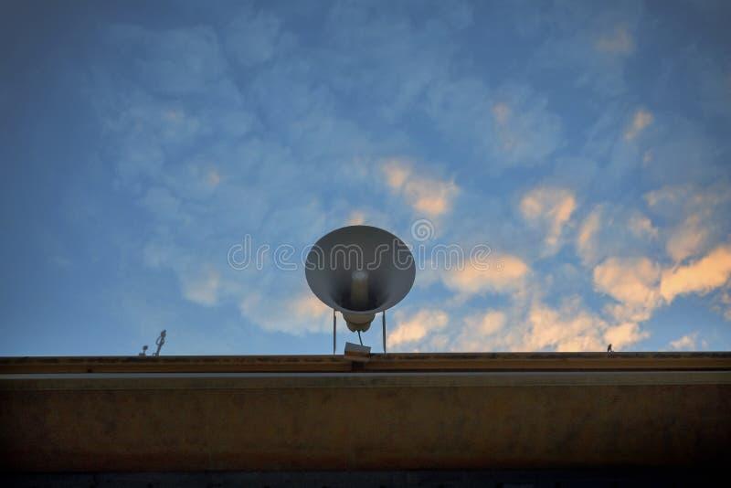 在修造的屋顶的扩音器反对美好的早晨五颜六色的天空 免版税库存图片