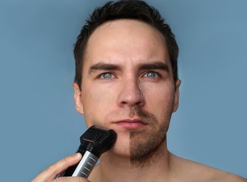 在修饰的年轻有胡子的人使用整理者的胡子期间 与胡子一半的半面孔被刮的 免版税库存图片