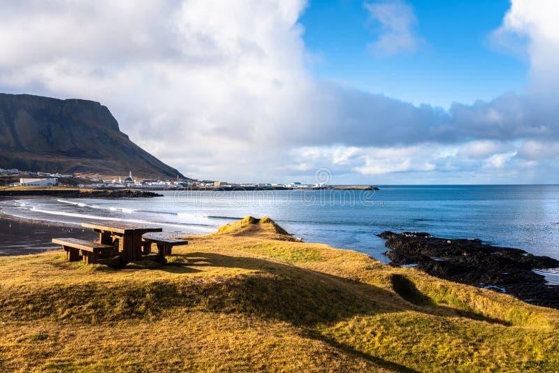 在俯视一个美丽的海湾的象草的Clifftop的空的野餐桌在冰岛在秋天 库存照片