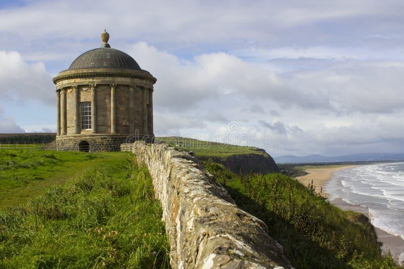 在俯视下坡海滩的clifftop边缘的古老Mussenden寺庙纪念碑在伦敦德里郡北爱尔兰 库存照片