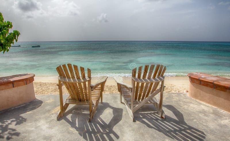 在俯视海洋的海滩的两把椅子 库存照片
