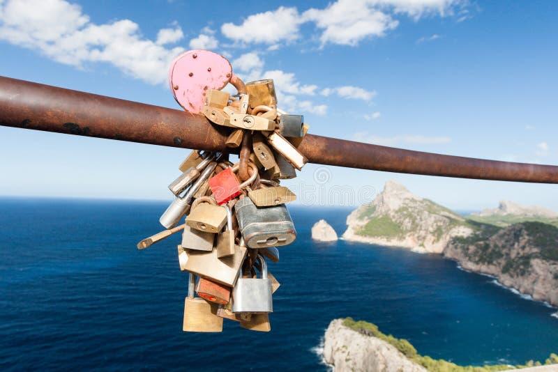 在俯视海洋的路轨的锁着的挂锁 库存照片