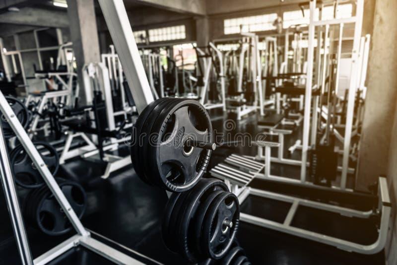 在俱乐部健身健身房的举重机架 爱好健美者肩膀的设备杠铃干涉行使和锻炼机器 免版税库存图片