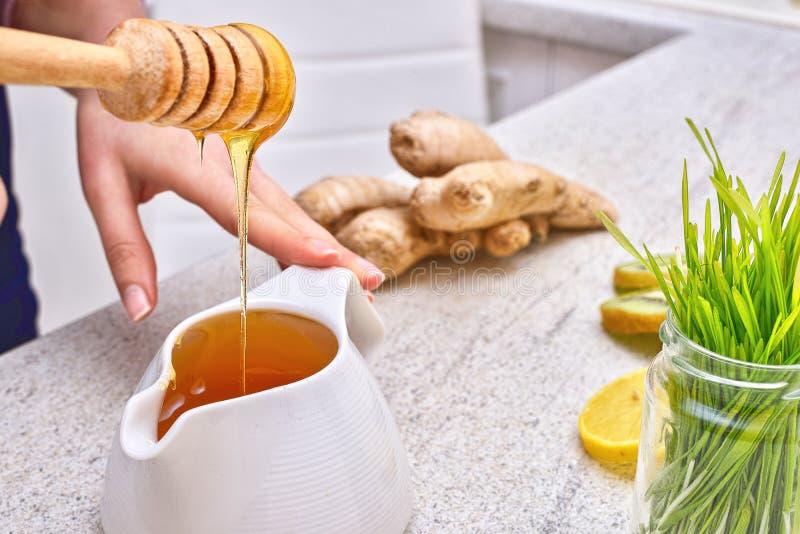 在倒绿色麦子、柠檬和姜戒毒所圆滑的人的滴水的金黄液体有机蜂蜜 图库摄影