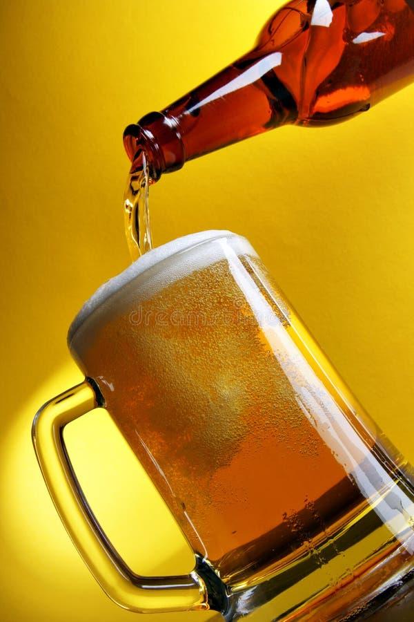 在倾吐的黄色的啤酒 免版税库存图片