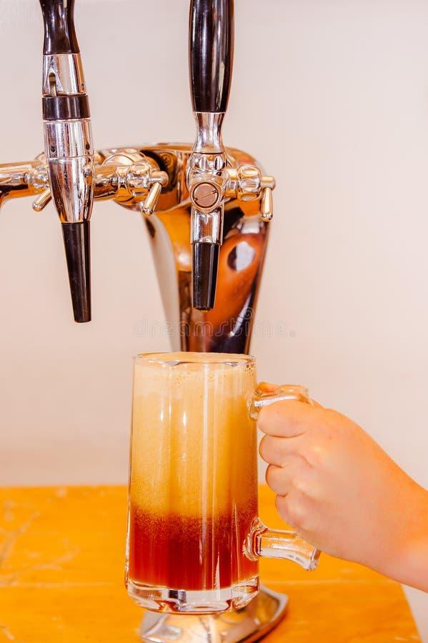在倾吐草稿储藏啤酒服务的啤酒轻拍的男服务员手在一间餐馆或客栈,在被弄脏的背景中 免版税库存照片