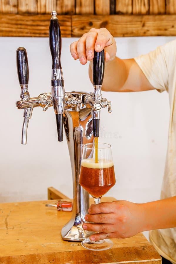 在倾吐草稿储藏啤酒服务的啤酒轻拍的男服务员手在一间餐馆或客栈,在被弄脏的背景中 免版税图库摄影