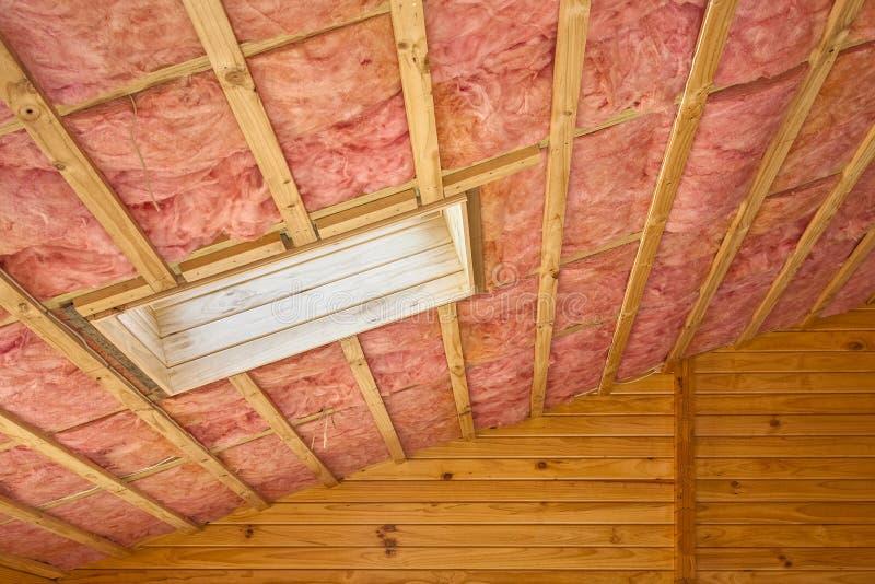 在倾斜的屋顶的桃红色玻璃纤维屋顶绝缘材料 库存照片