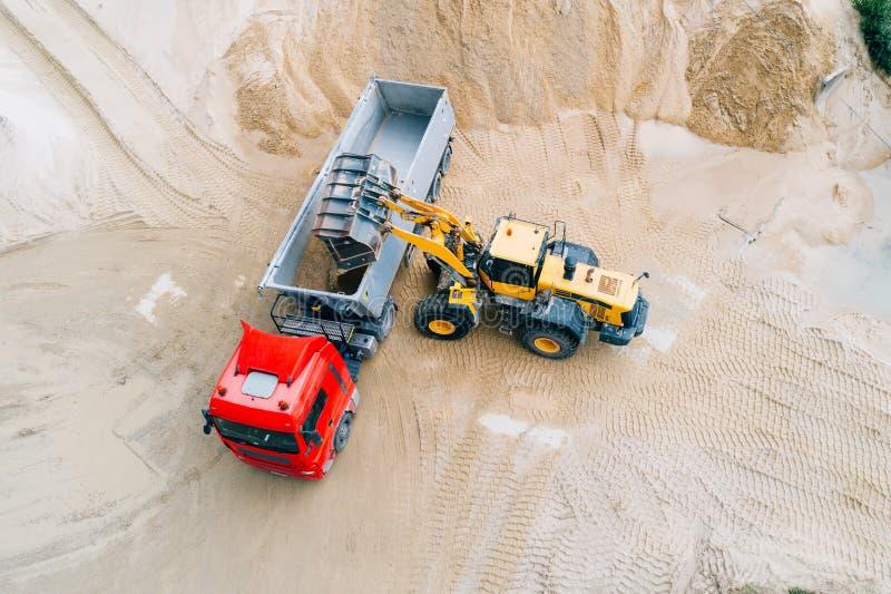 在倾销者卡车的黄色轮子装载者装货沙子 库存图片