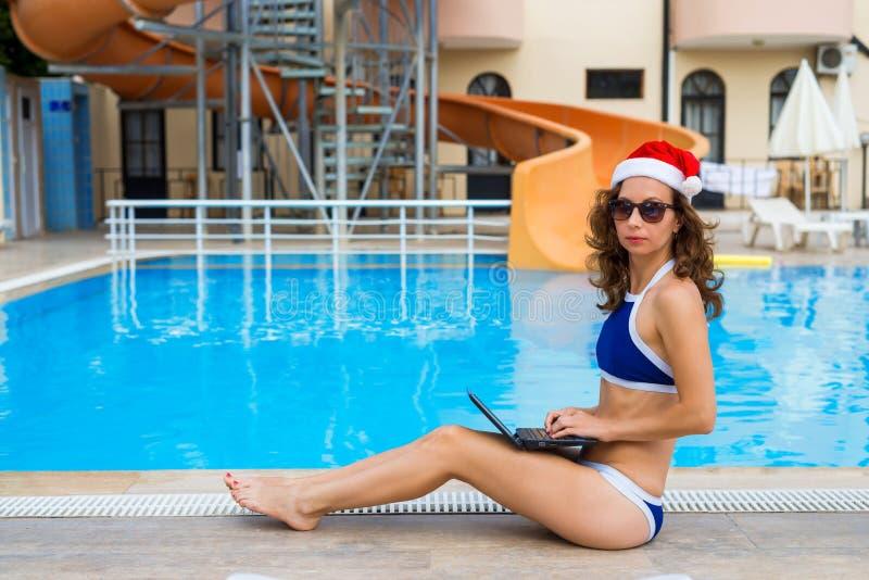 在假日期间,工作,妇女遇见圣诞节在一个热带国家 圣诞老人项目帽子工作的年轻女人在膝上型计算机坐 免版税库存照片