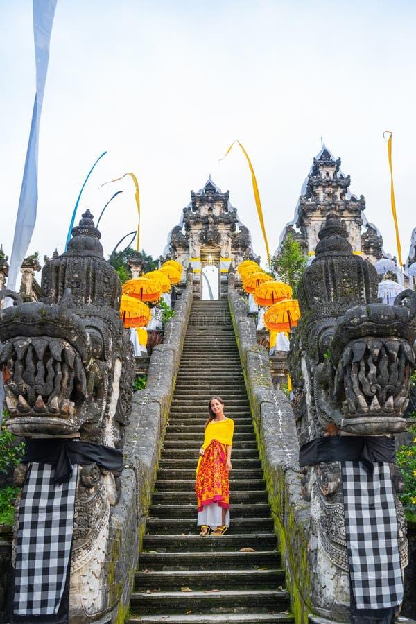 在假日装饰的巴厘语寺庙的由下往上的看法Galungan 在台阶的妇女身分 r 免版税库存图片