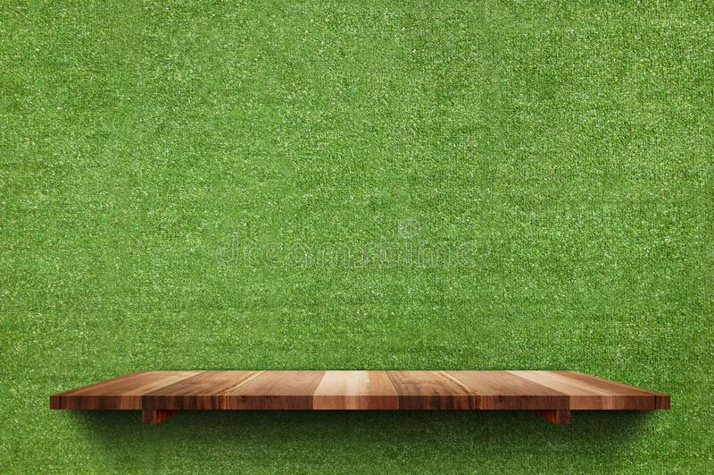 在假绿草墙壁背景,嘲笑的空的木委员会架子 图库摄影